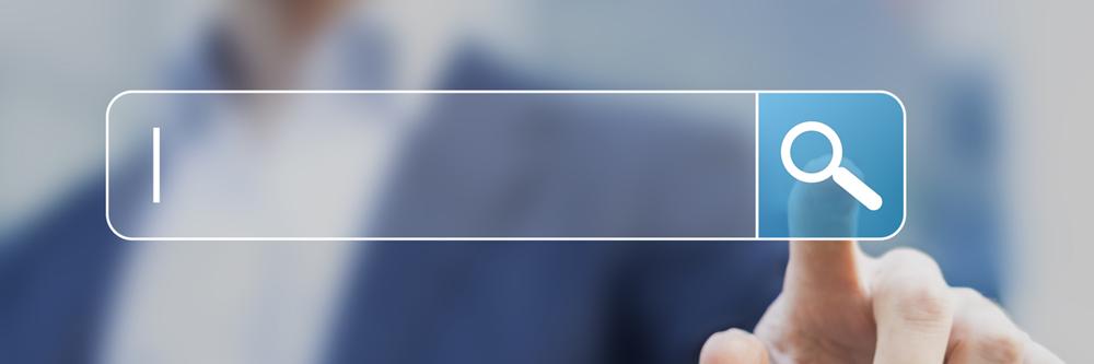 Symbolbild Suche: Zeigefinger tippt auf Lupe neben einem Eingabefeld für Suche